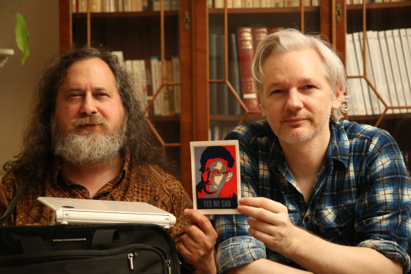 Richard Stallman and Julian Assange, holding a photo of Edward Snowden